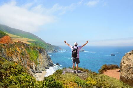 Man  standing on the top of the mountain with her  hands up looking at beautiful coastal ocean mountain landscape during  hiking trip.  Pacific Ocean.Big Sur, California, USA Stock fotó