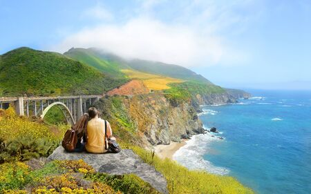 Couple looking at beautiful coastal mountain landscape on hiking trip. Bixby Bridge, Big Sur, California, USA