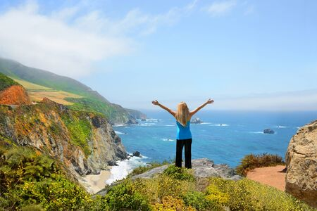 Woman standing on the top of the mountain with her hands up looking at beautiful coastal ocean mountain landscape during hiking trip. Pacific Ocean.Big Sur, California, USA
