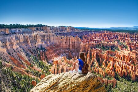 Girl sitting on the top of the mountain looking at beautiful view. Woman relaxing on the rock on summer vacation hiking trip. Inspiration Point. Bryce Canyon National Park,Utah, USA
