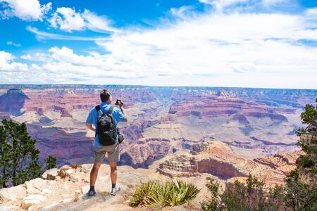Man standing on top of the mountain using his camera. Man enjoying his summer vacation trip. South Rim, Grand Canyon National Park, Arizona, USA. Stock fotó