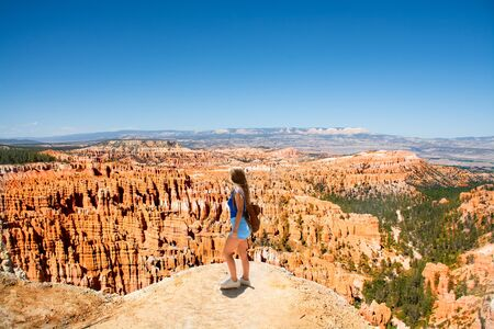Girl standing on the top of the mountain looking at beautiful view. Woman enjoying time on hiking trip. Bryce Canyon National Park,Utah, USA