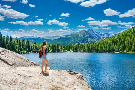 Girl  relaxing by the lake. Woman standing on the rock looking at beautiful summer mountain landscape, enjoying time  on hiking trip. Bear Lake, Rocky Mountains National Park, Colorado ,USA.