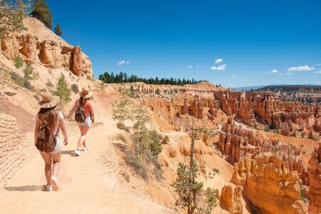 Girls on summer vacation hiking trip. Friends hiking on footpath in red mountains. Bryce Canyon National Park, Utah, USA