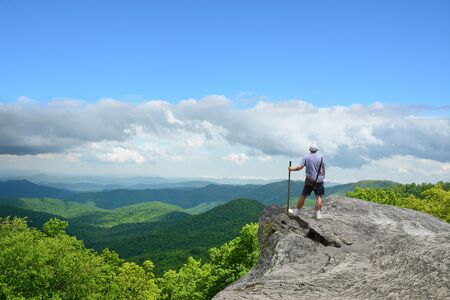 Hiking in the mountains. Man standing on top of the mountain on edge of cliff, looking at beautiful summer Blue Ridge Mountains landscape. North Carolina, USA