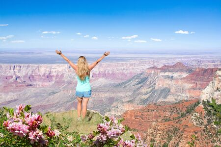 Woman with raised hands relaxing on top of the mountain, looking at beautiful summer landscape.Hiking trip. North Rim. Grand Canyon National Park, Arizona, USA.