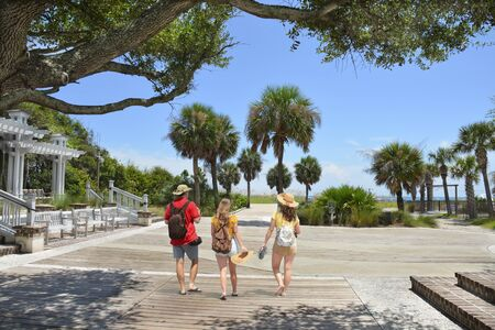 Family walking to the beach on summer vacation. People enjoying summer vacation by the ocean. Palm trees on the pathway leading to ocean. Coligny Beach Park, Hilton Head Island, South Carolina, USA
