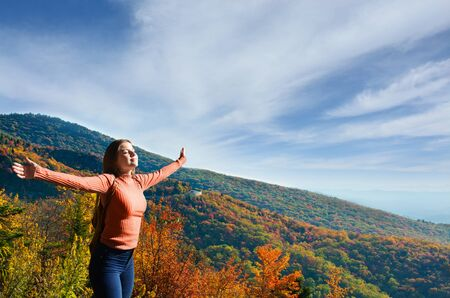 Joy and freedom.Young woman enjoying life outdoors. Smiling, happy girl with outstretched arms in the autumn mountain scenery. Blue Ridge Parkway, Close to Blowing Rock, North Carolina,USA.