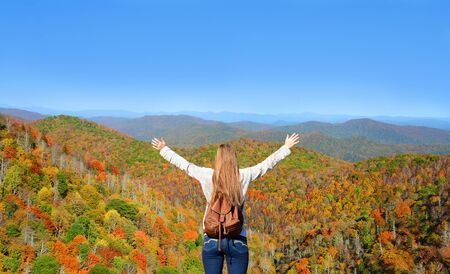 Girl enjoying time on top of the mountain on her fall hiking trip. Blue Ridge mountains, North Carolina. USA.