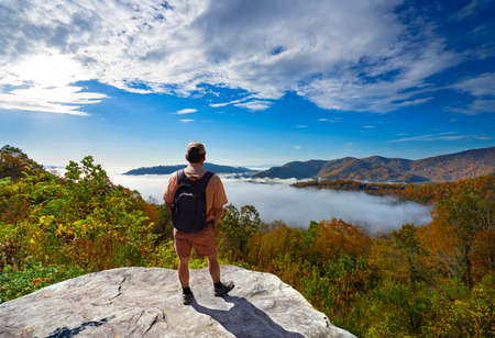 Man on hiking trip, standing on top of the mountain over the clouds, enjoying beautiful autumn mountain scenery. Hiker looking at beautiful view. Blue Ridge Mountains, North Carolina, USA.