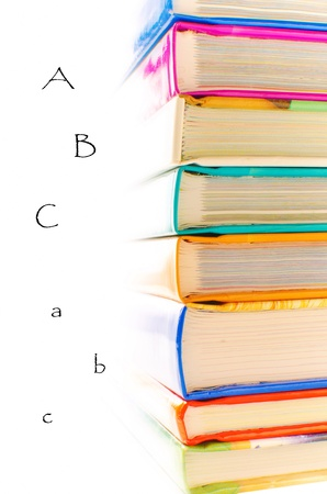Forefront of a group of books stacked, with letters on white background