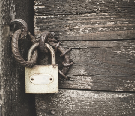 door lock: Old padlock on a wooden door Stock Photo
