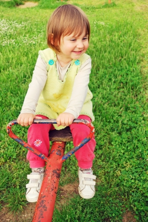 Happy little girl swinging on see-saw photo