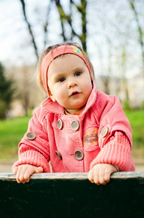 sincere girl: Baby girl standing on a bench in park