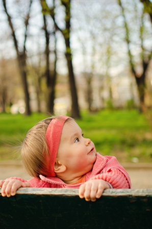 Baby girl in park looking up photo