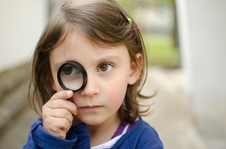Girl holding magnifying glass photo