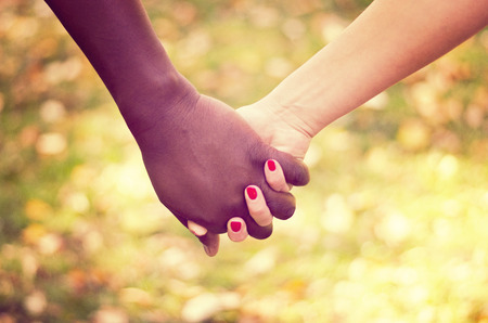 mixed race person: Close up on a couple holding hands in the park Stock Photo