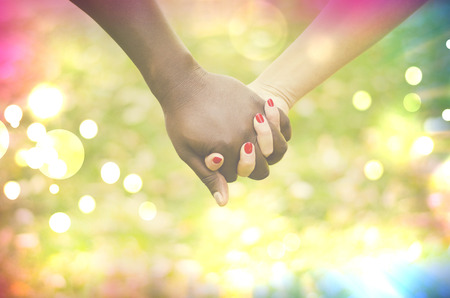 mixed races: Close up on a mixed race couple holding hands in the park Stock Photo