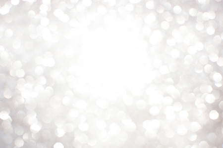 celebration champagne: Silver white glittering Christmas lights. Blurred abstract background