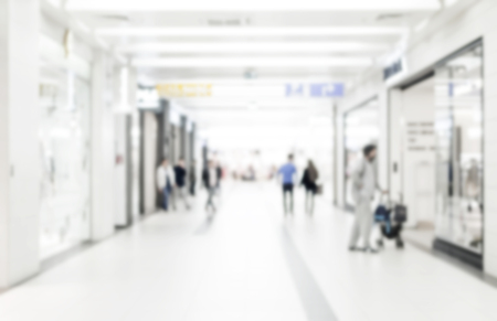 blurred background: Blur store with bokeh background. Silhouettes of Business People in Blurred Motion Walking. Business people walking in the office corridor.