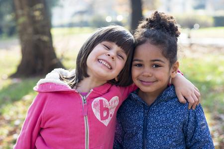 niños diferentes razas: Concepto de amistad sin fronteras raciales, dos amigas abrazando, chica en blanco y negro en un brillante día de otoño en el parque