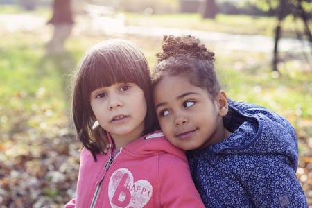 niños diferentes razas: concepto de amistad sin límites raciales, dos amigas abrazos, chica blanco y negro en un brillante día de otoño en el parque