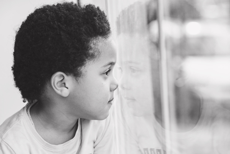 cute Afro american boy looking through the window