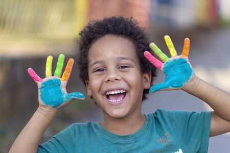 beautifu happy boy with colorful painted hands Banque d'images