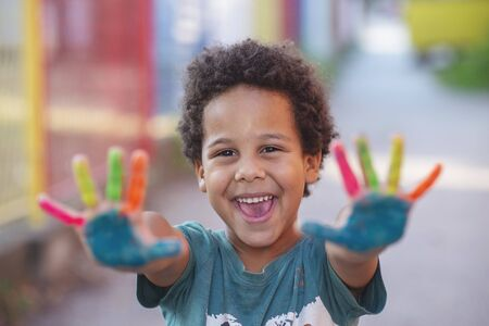 beautiful happy boy with painted hands