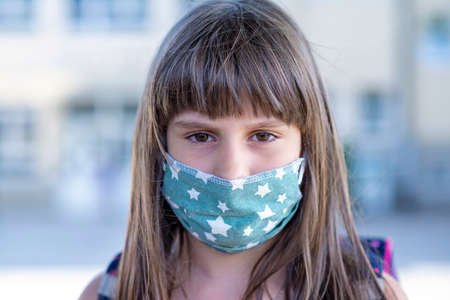 Girl wearing face mask during corona virus and flu outbreak. Worried girl looking at the camera. Archivio Fotografico