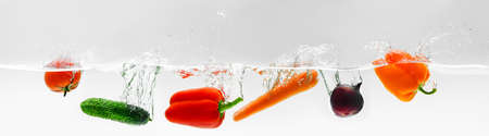 Beautiful ripe vegetables fall with a splash into the water, healthy vegetarian food from an organic farm