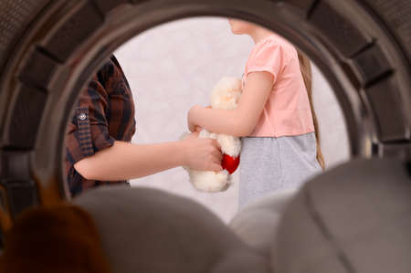The mother takes the child's favorite soft toy to wash it in the washing machine. The concept of the need for periodic washing of toys for their cleaning and disinfection. 版權商用圖片
