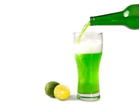 St. Patrick's Day from a bottle in a beer glass pours a traditional green Irish beer with thick foam on an isolated background.