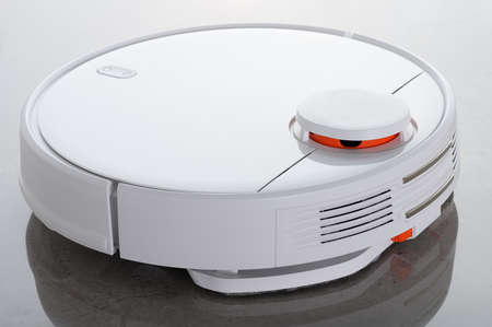 White robot vacuum cleaner with wet cleaning function, against the background of mirrored gray granite very close-up.