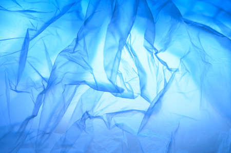 Abstract background of folds of thin plastic, gradient blue color.