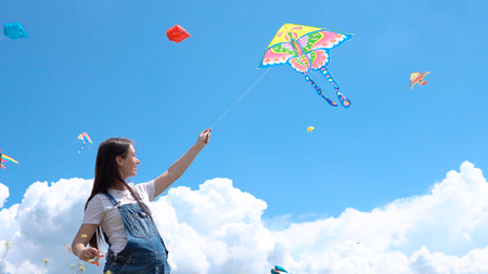 A, young, pregnant, girl, jumpsuit, launches, kite, against, blue, sky, clouds Imagens