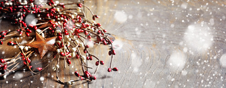 country christmas: Christmas wreath with berries and rusty stars on wooden background. Falling snow effect. Vintage Style. Long narrow format. Copy space. Stock Photo