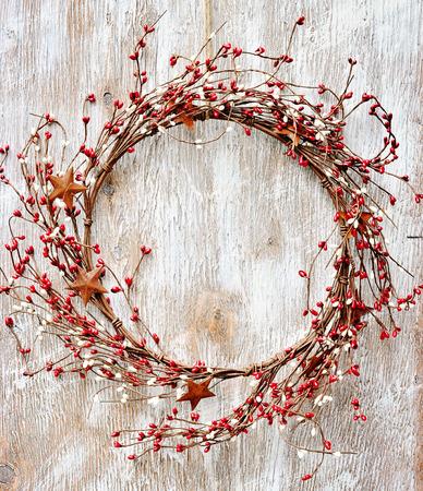 madera r�stica: Corona de Navidad con bayas rojas y blancas y estrellas de metal oxidado en el fondo de madera. Estilo vintage Foto de archivo