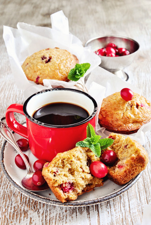 bakery products: Oatmeal muffins with fresh cranberries, and coffee in enamel mug for breakfast, selective focus, toned image. Stock Photo