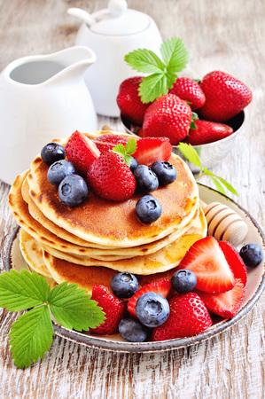 colazione: Pila di frittelle con fragole fresche, mirtilli, sciroppo d'acero e miele per la prima colazione, la tavola, messa a fuoco selettiva, tonica immagine