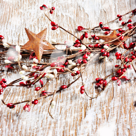 tradition: Christmas wreath with red and white berries and rusty metal stars on wooden background. Falling snow effect. Vintage Style