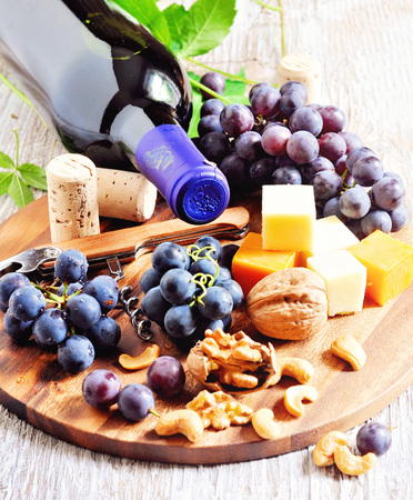 cashews: Red wine, grapes, cheese, walnuts and cashews on wooden background.
