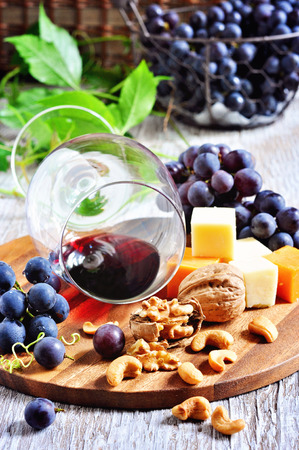 Red wine, grapes, cheese, figs, walnuts and cashews on wooden background.