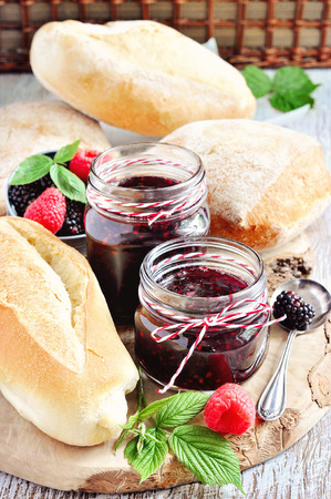pectin: Fresh bread and homemade blackberry and raspberry jam in jars for breakfast. Stock Photo