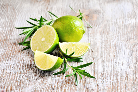 Fresh green lime and rosemary herb on wooden background.