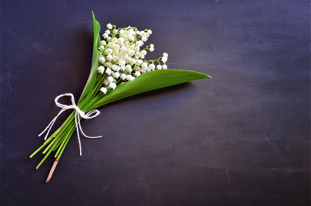 Bouquet of lilly of the valley flowers on dark background.