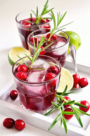 cocktail glasses: Red refreshing cranberry drink with rosemary, lime, and ice cubes, summer cocktail.