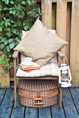vintage objects: A cup of coffee on a chair on a terrace or a patio. Vintage objects, lamp, picnic basket, pillows, books. Stock Photo