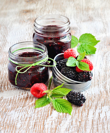 pectin: Homemade blackberry and raspberry jam in jars and fresh berries for breakfast.