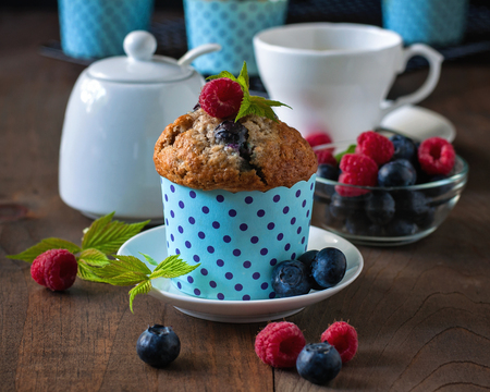 blueberry muffin: Muffins with blueberries and raspberries, summer, healthy breakfast, selective focus, toned image, wooden background Stock Photo
